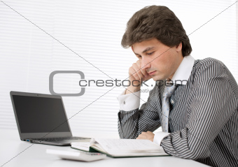 Portrait of a young businessman thinking while working on laptop