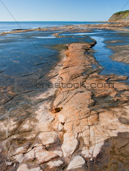 Kimmeridge Bay seascape with rock ledges extending out to sea on