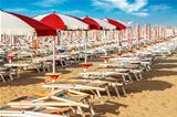 red and white umbrellas and sun loungers on the sandy beach
