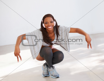 Pretty young African American woman dancing with delight and wearing headphones