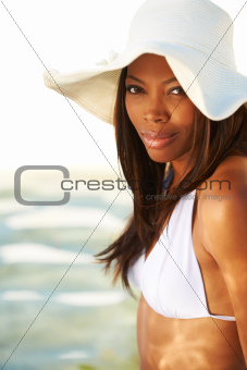 Pretty African American woman wearing a sunhat and a white bikini