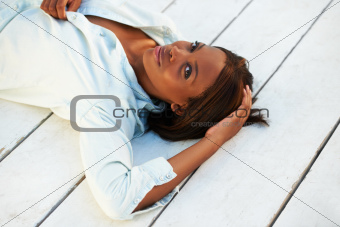 Pretty young African American woman lying on a wooden floor