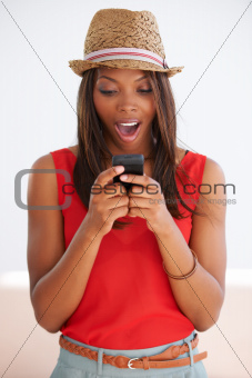 Surprised African American woman typing a text message on her cellphone