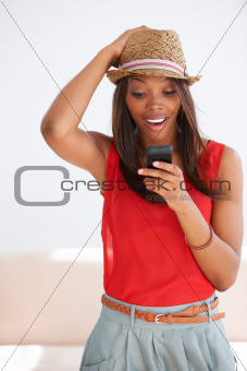 Smiling African American woman typing a text message on her cellphone