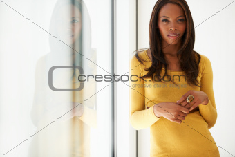 Stylish young African American woman standing alongside a window