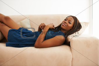 Happy young African American woman lying on the sofa at home