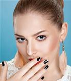 Young cute woman touching her clean face. Bright manicure