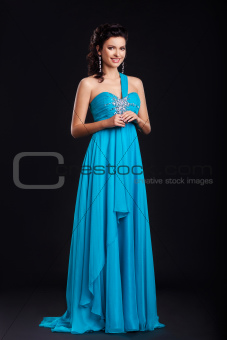 Portrait of trendy young woman in trendy blue dress smiling