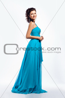 Feminine. Gorgeous graceful smiling brunette girl in blue dress