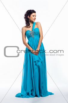 Fashion woman in modern fashion long blue dress posing