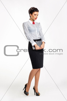 Thoughtful business lady in fashion skirt and blouse with book