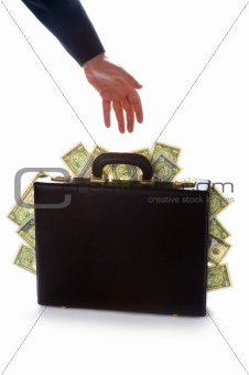 businessman reaching for a briefcase full of money