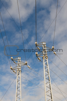 High Voltage Poles under blue Sky and clouds