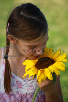 Young girl smelling a sunflower