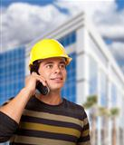 Handsome Hispanic Male Contractor on Cell Phone in Front of Corporate Building.