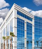 Dramatic Reflective Corporate Building with Blue Sky and Clouds.