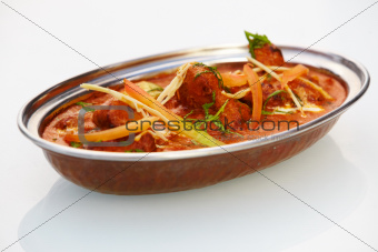 A delectable meat dish served in a sea of delicious sauce topped in complimentary relish