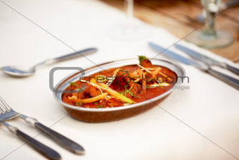 A delectable meat dish served in a sea of delicious sauce topped in complimentary herbs and vegetables