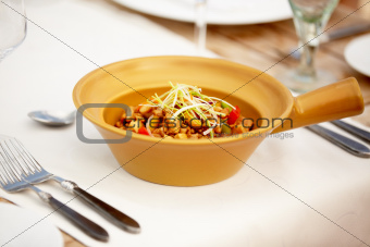An appetizing dish presented in a beige bowl set invitingly upon the dining table