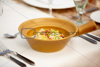 An appetizing rice dish presented in a beige bowl and set invitingly upon the dining table
