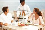 A waiter presents a couple with their main course - a selection of meats on a rack