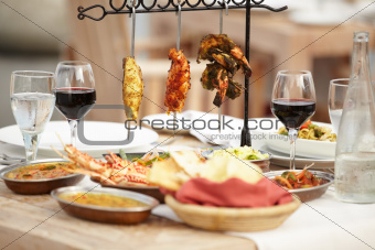 A selection of meats sitting invitingly upon a dining table with an assortment of food dishes