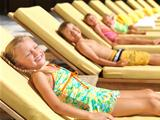 Cute little kids sunbathing by a pool