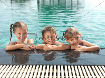 Cute little kids in swimming pool enjoying vacations