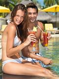 Young couple enjoying cocktail by the poolside