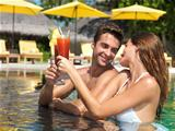 Attractive couple drinking cocktails in the pool