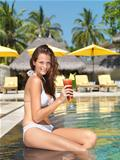 Beautiful woman enjoying a cocktail by the pool