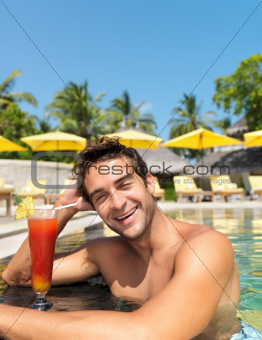 Happy young guy in the pool with a cocktail