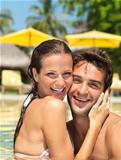 Cheerful couple having fun in the pool