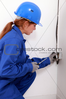Young female trades apprentice wiring a power point
