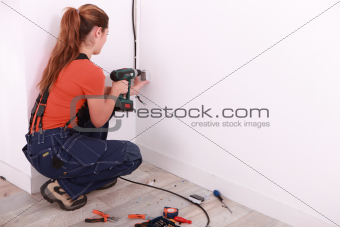 Woman drilling hole in wall