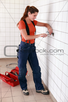 Female electrician working in bathroom