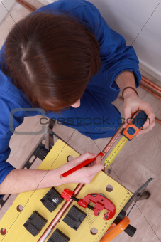 a female technician working on a copper tube