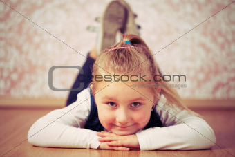 beautiful little girl lying on floor