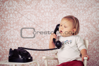 little baby with old vintage phone