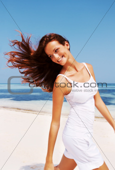 Beautiful young female walking on a beach