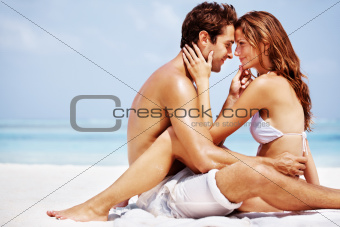Happy young couple at the beach in romantic mood - Copyspace