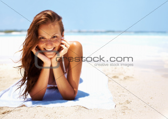 Portrait of young woman giving beautiful smile while relaxing on beach