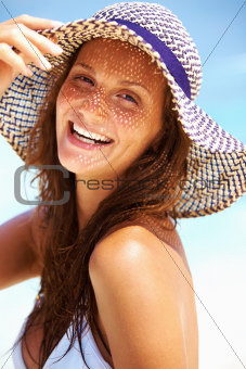 Closeup of young woman looking at you in beach hat