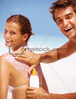 Portrait of happy young couple applying sun block lotion for preventing sunburn