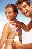 Portrait of cheerful young man applying anti tanning lotion on woman&#39;s back