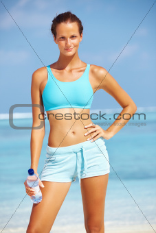 Portrait of enthusiastic athlete smiling after exercising on beach