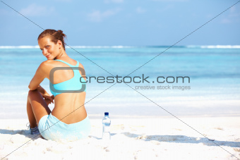 Portrait of lovely young woman looking at you after workout on beach