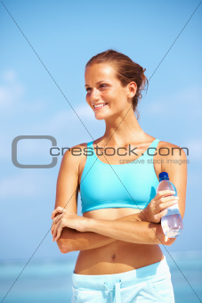 Portrait of healthy young athlete smiling with water bottle on the beach