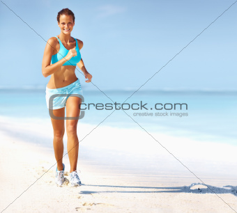 Portrait of happy young woman jogging on the beach