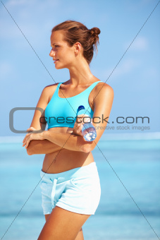 Portrait of lovely female athlete standing with confidence on beach